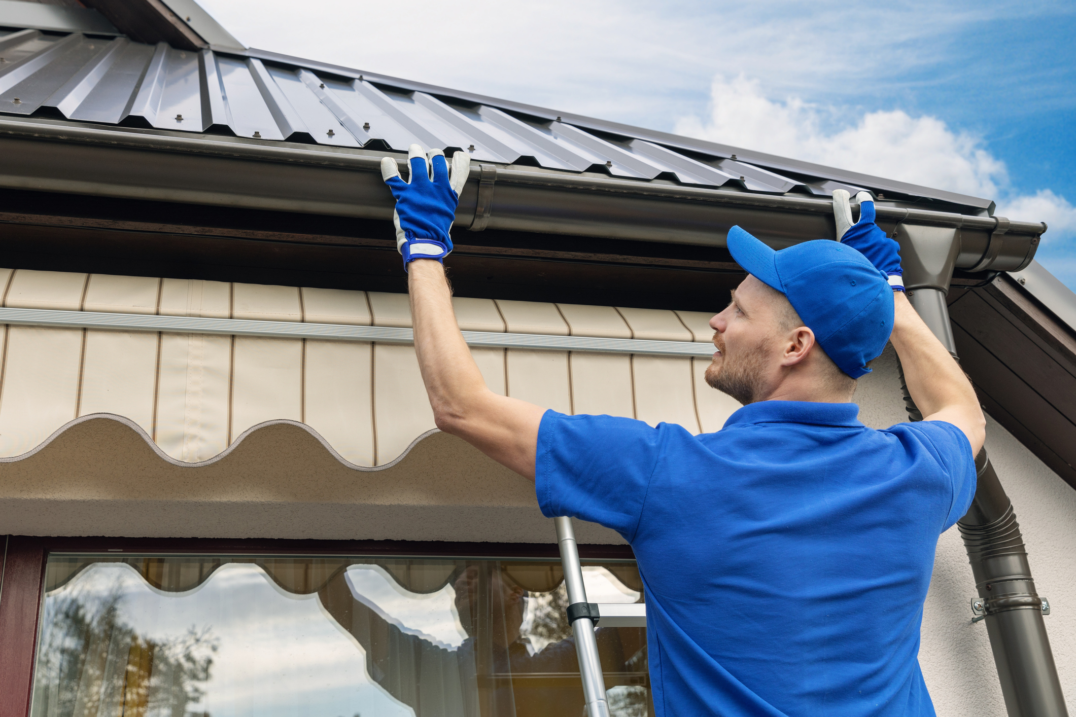 man in blue shirt and hat fixing gutters on the side of a house